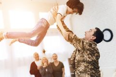 Young son meets a man in camouflage at home. The family meets a men in camouflage at home. He returned from the army. They are happy to see him. They embrace Royalty Free Stock Photo
