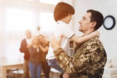 Young son meets a man in camouflage at home. The family meets a men in camouflage at home. He returned from the army. They are happy to see him. They embrace Royalty Free Stock Photography