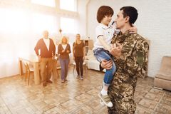 Young son meets a man in camouflage at home. The family meets a men in camouflage at home. He returned from the army. They are happy to see him. They embrace Royalty Free Stock Images