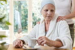 Family member supporting sick elderly woman with cancer stock image
