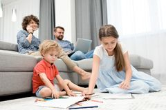 Family Members Enjoying Sunday. Ordinary day of large family: curly little boy and his elder sister sitting on carpet and drawing pictures with pencils while Stock Photo