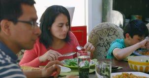 Family members having lunch on dining table 4k. Family members having lunch on dining table at home 4k