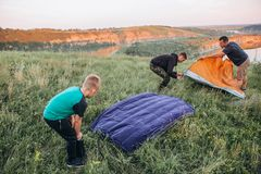Family men weekend tent canyon overnight stay. Family men a weekend with a tent top a canyon by a winding river preparation for an overnight stay stock photos