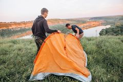 Family men weekend tent canyon overnight stay. Family men a weekend with a tent top a canyon by a winding river preparation for an overnight stay royalty free stock image
