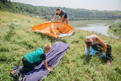 Family men weekend tent canyon overnight stay. Family men a weekend with a tent top a canyon by a winding river preparation for an overnight stay royalty free stock photos