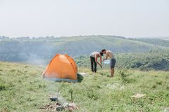 Family men weekend tent canyon overnight stay. Family men a weekend with a tent top a canyon by a winding river preparation for an overnight stay stock image