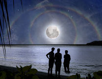 Family, miracle moon rainbow. Paradise mystery. Paradise beach. The young family, father, mother, daughter is watching on miracle of moon rainbow. The beautiful Royalty Free Stock Photography