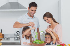 Family mixing a salad together. In the kitchen Stock Photo