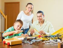 Family modeling something with instruments. Happy family of three with teenager modeling something with instruments Stock Images