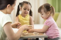 Family at the table playing board game. Family mom and children at the table playing board game Stock Photos