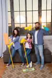 Family mom dad and daughter with cleaning supplies at living room. We love cleanliness and tidiness. Cleaning together. Easier and more fun. Family care about stock photos