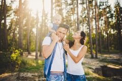 Family mom, dad and daughter sits at the daddy on the shoulders, and parents kiss on the nature in the forest in the summer at sun. Set stock photos