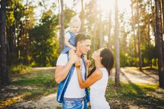 Family mom, dad and daughter sits at the daddy on the shoulders, and parents kiss on the nature in the forest in the summer at sun royalty free stock photography