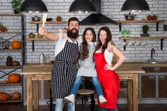 Family mom dad and daughter wear aprons stand in kitchen. Cooking food concept. Prepare delicious meal. Breakfast time. Family having fun cooking together stock image