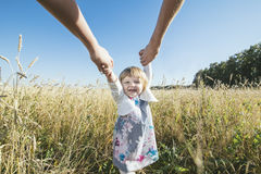 Family, mom, dad holding the daughter hands happy and beautiful Stock Images