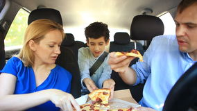 Family, mom, dad and son eating pizza in the car