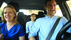 Family, mom dad and son riding in car, they sing songs with the whole family stock video footage