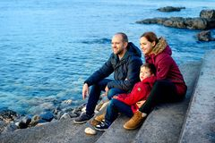Family mom, dad and son are sitting on the beach by the sea and looking into the distance. Season - spring, autumn. The Royalty Free Stock Image