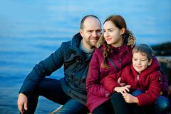 Family mom, dad and son sitting on the beach by the sea. Season - spring, autumn. The concept of family happiness Stock Photo