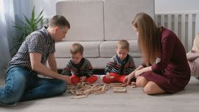 Family mom, dad and two twin brothers play together building out of wooden blocks on the floor. Family mom, dad and two twin brothers play together building out stock video footage