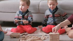 Family mom, dad and two twin brothers play together building out of wooden blocks on the floor. Family mom, dad and two twin brothers play together building out stock footage
