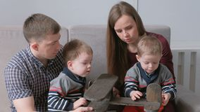 Family mom, dad and two twin brothers play together with wood airplane sitting on the sofa. Family mom, dad and two twin brothers play together with wood stock video