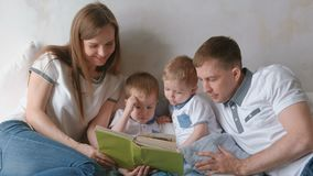 Family mom, dad and two twin brothers read books laying on the bed. Family reading time. Family mom, dad and two twin brothers read books laying on the bed stock video footage