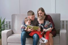 Family mom, dad and two twin brothers read books sitting on the sofa. Family reading time. stock images