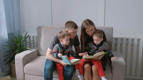 Family mom, dad and two twin brothers read books sitting on the sofa. Family reading time. Family mom, dad and two twin brothers read books sitting on the sofa stock footage