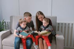 Family mom, dad and two twin brothers read books sitting on the sofa. Family reading time. Family mom, dad and two twin brothers read books sitting on the sofa royalty free stock photo