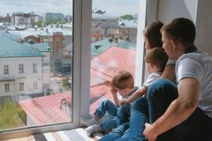 Family mom, dad and two twin brothers toddlers look out the window at the city. stock photos