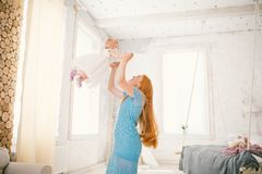 Family mom and daughter one year old entertain themselves inside the interior. The woman puts the child`s arms up and pushes her Royalty Free Stock Photography