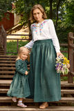Family mom with daughter in vintage retro style linen dresses with bouquet walking dawn wooden stairs in a park garden stock photography