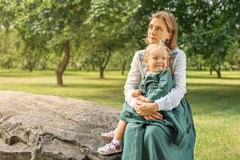 Family mom with daughter in vintage retro linen dresses sitting on a stone rock in the park forest in a thoughtful state and. Family mom with daughter in vintage stock photography