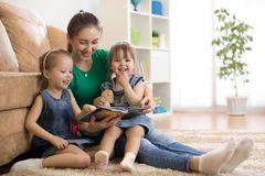 Happy mother and little daughters reading a book together in the living room at home. Family activity concept. Family mom and daughters relaxing at home and royalty free stock photography