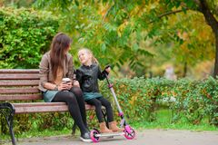 Family of mom and kid outdoors in autumn day. Young mother with cute little girl in autumn park on sunny day Royalty Free Stock Photo