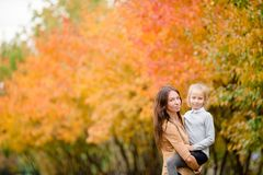 Family of mom and kid outdoors in autumn day. Young mother with cute little girl in autumn park on sunny day Royalty Free Stock Image