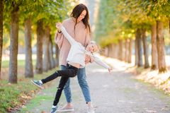 Family of mom and kid outdoors having fun in autumn day. Young mother with cute little girl in autumn park on sunny day Royalty Free Stock Photos