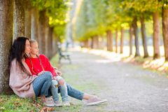 Family of mom and kid outdoors in park at autumn day. Young mother with cute little girl in autumn park on sunny day Stock Photo