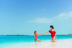 Family of mom and kid in shallow water. Young mother and little daughter on beach holiday. Mother and little daughter enjoying time at tropical beach Stock Photography