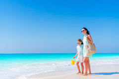 Family of mom and kid walking on white beach. Beautiful mother and her adorable little daughter at beach Royalty Free Stock Image