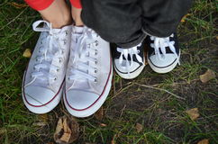 Family. Mom and son legs on the grass in the sneakers Stock Image