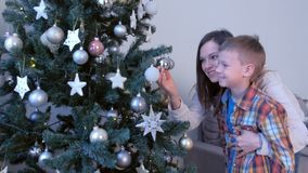 Family mom son looking in reflection in gold ball on Christmas tree together. stock footage