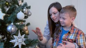 Family mom son playing with toys balls and stars on Christmas tree together. stock footage