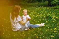 Family. Mom and son are sitting in meadow. Girl put small boy to her knees. Yellow dandelions grow in meadow royalty free stock image