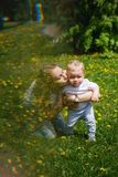 Family. Mother and son. Kiss. Family. Mom and son are walking in meadow. Girl kneels, hugs and kisses little boy Royalty Free Stock Images