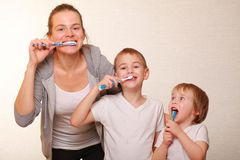 Mom and two blond boys brush their teeth. Family mom and two blond boys brush their teeth royalty free stock images