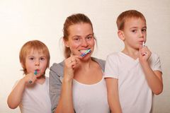 Mom and two blond boys brush their teeth. Family mom and two blond boys brush their teeth stock photos