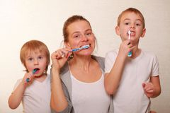 Mom and two blond boys brush their teeth. Family mom and two blond boys brush their teeth stock photo