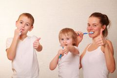 Mom and two blond boys brush their teeth. Family mom and two blond boys brush their teeth royalty free stock photos